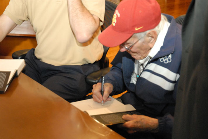 Louis Zamperini signs books at the Billy Graham Library in June of 2011.