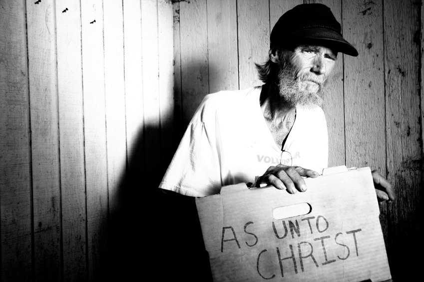 "Man holding sign that reads, ""As unto Christ"""