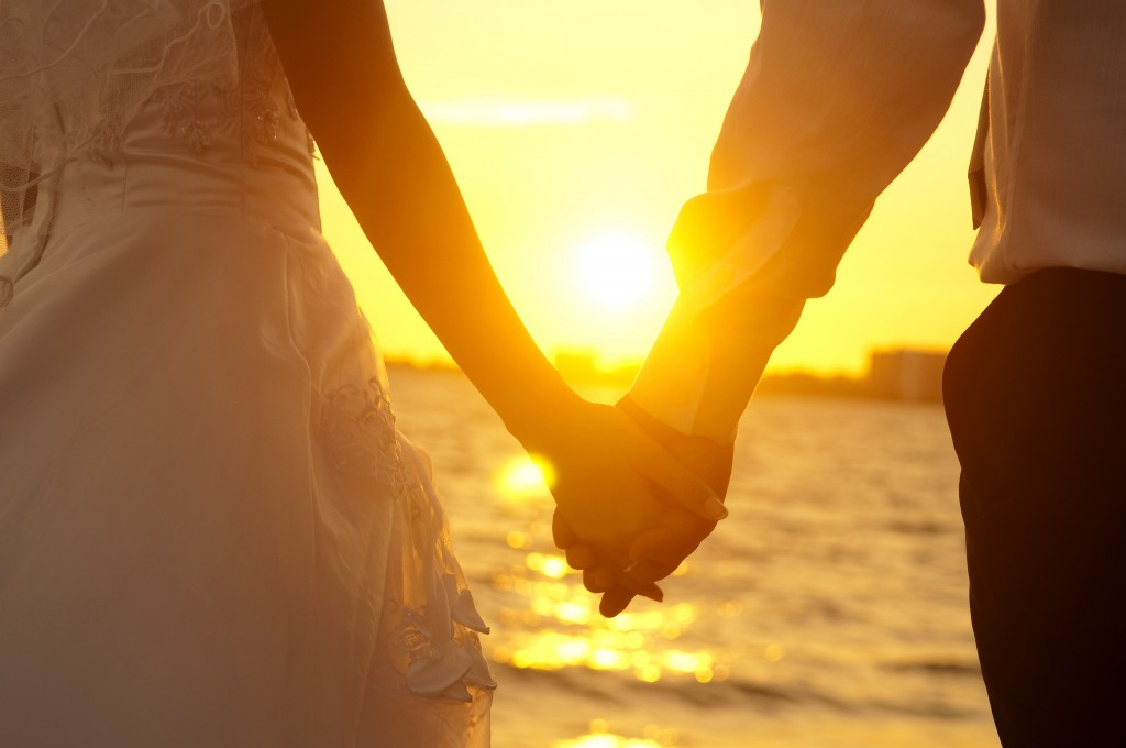 Bride and groom holding hands in front of sunset