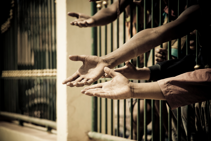 hands reaching out of jail cell