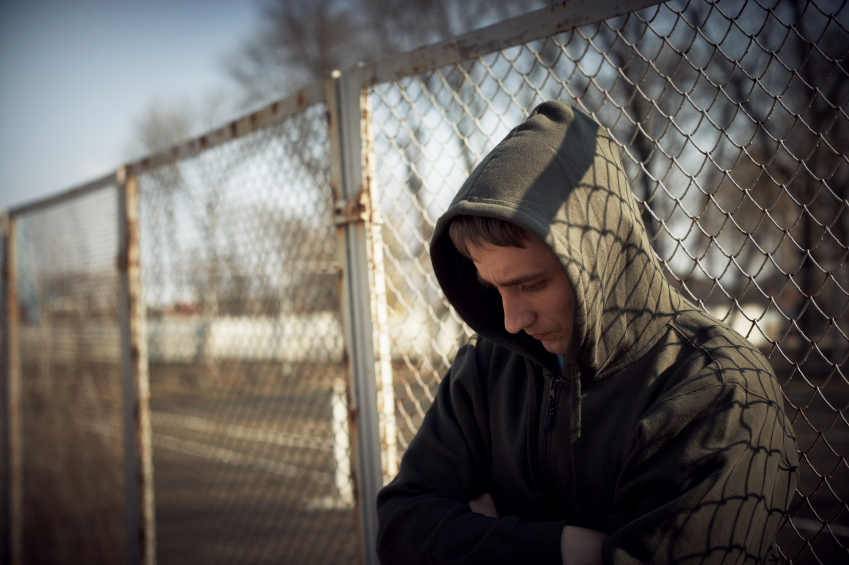 guy in hoodie against fence