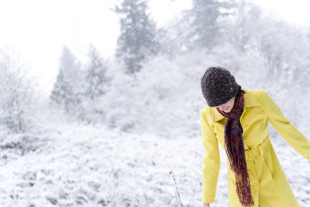 woman in snow wearing yellow coat