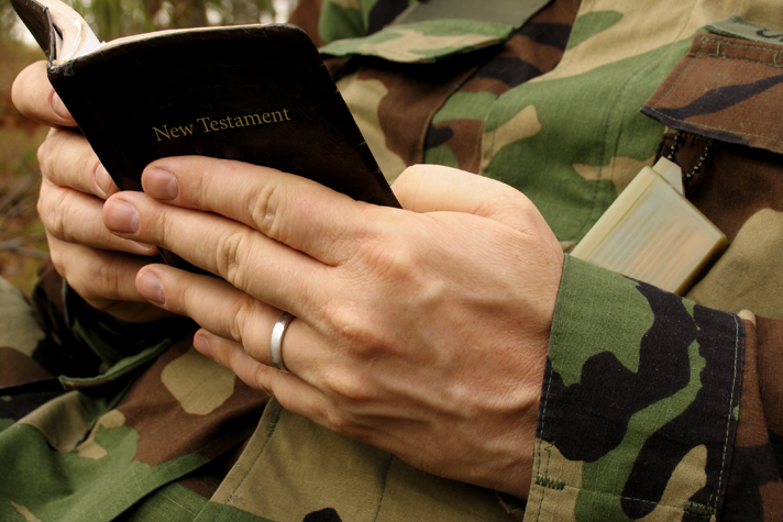 military man reading Bible