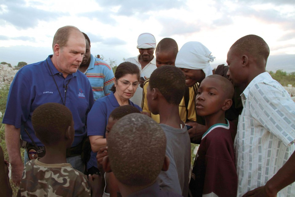 Billy Graham Rapid Response Team Chaplains Phil & Pam Rhodes share with young Haitian men and boys following the earthquake in Haiti.