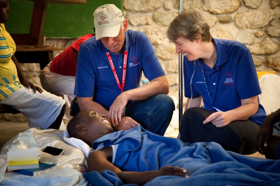 Billy Graham Rapid Response Team Chaplains Jack & Becca Dowling visit with Watson, a Haitian man whose leg was badly damaged during the Haiti earthquake.