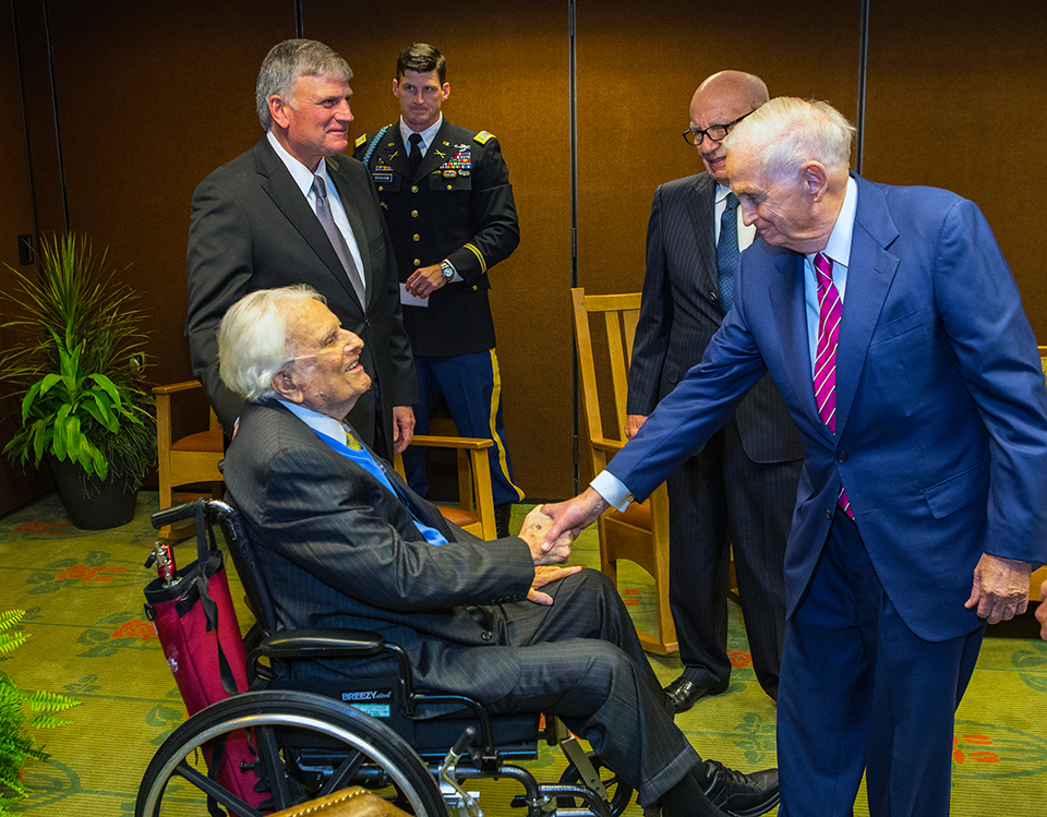 Bill Marriott, Jr greeting Billy Graham as Franklin Graham, Edward Graham and Rupert Murdoch stand nearby.