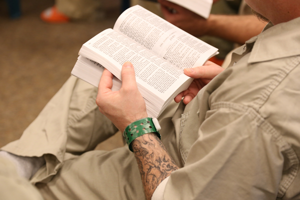 An inmate reads from the Gospel of John.