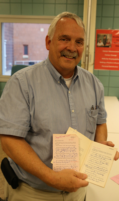 Chaplain Jim Bzoskie holds a handwritten Bible study he completed after giving his life to Christ. He received the booklet from BGEA in the '70s and corresponded with someone from the ministry.