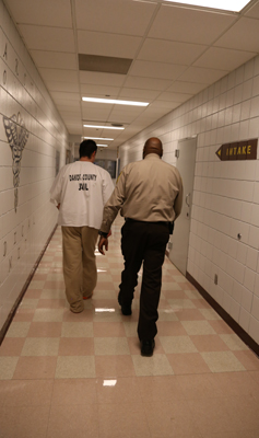 An inmate walks down the hall with Operations Lt. Lawrence Hart, a fellow Christian.