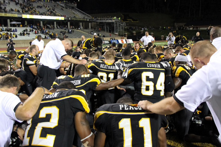 Coaches and players from the Appalachian State University football team gather for prayer.
