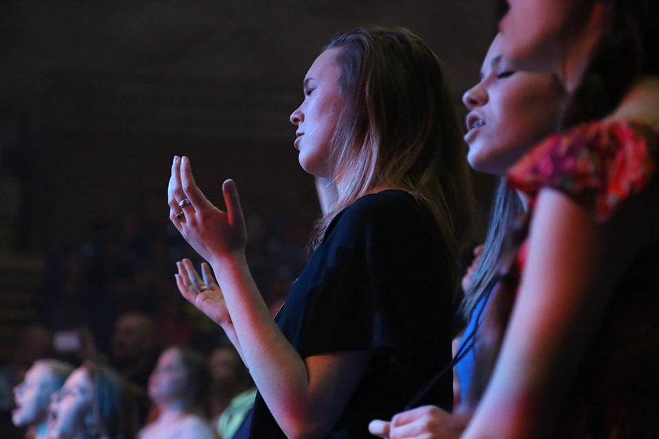 A young woman worships while the Rhett Walker Band plays.