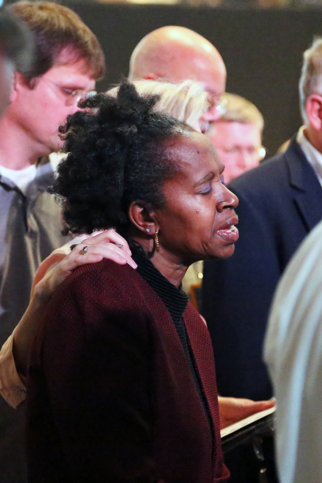 A woman prays after coming forward during the invitation to accept Christ.