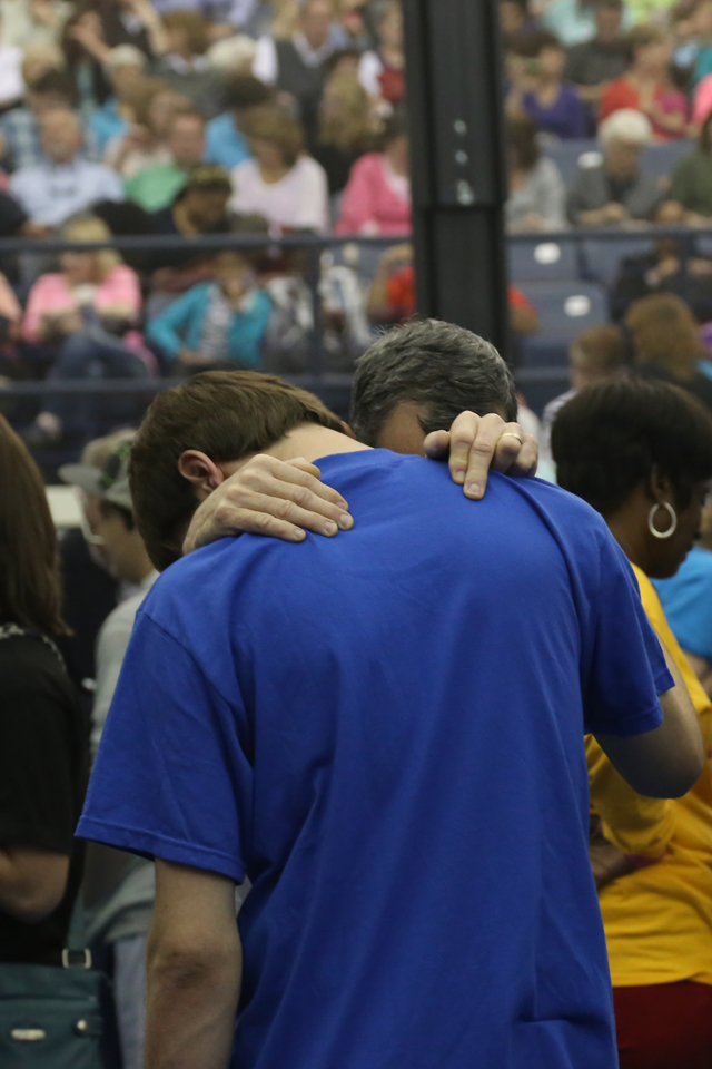 A counselor prays with a young man who came forward during the invitation.