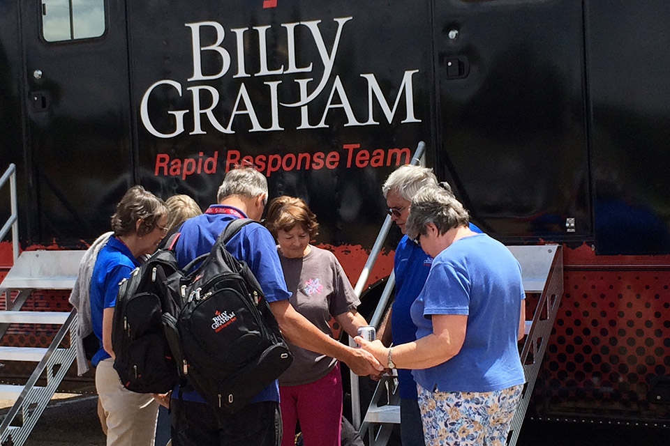 Rapid Response Team chaplains Al and Toni New, along with Mike and Pookie Mattingly, pray with two Louisville, Miss., residents outside the RRT Mobile Command Center on Wednesday afternoon. You can help give the hope and love of Christ by praying for and supporting this chaplaincy ministry at BillyGraham.org/Response.