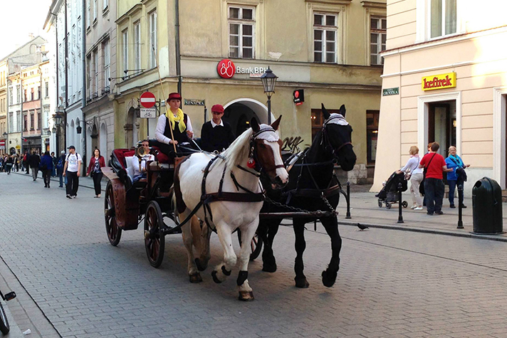 A horse-drawn carriage travels around the square in Kraków, Poland. Thousands of people will make the journey from their hometowns all across Poland to Warsaw for the June 14-15 Festival of Hope.