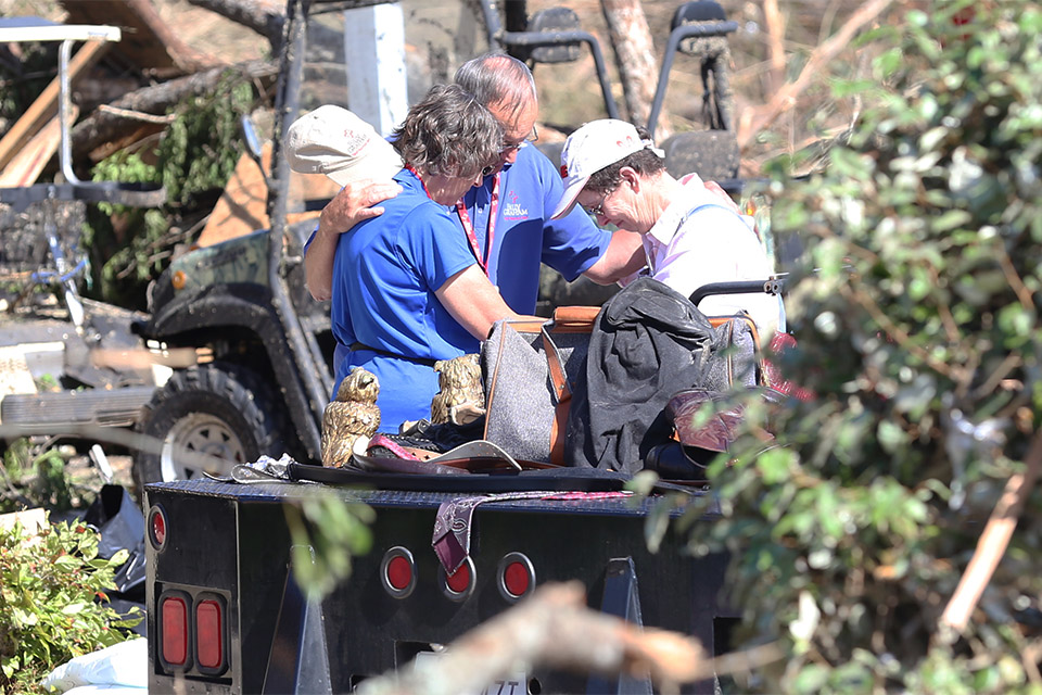 Rapid Response Team chaplain pray with a family member of a homeowner who lost everything in Monday's tornado.
