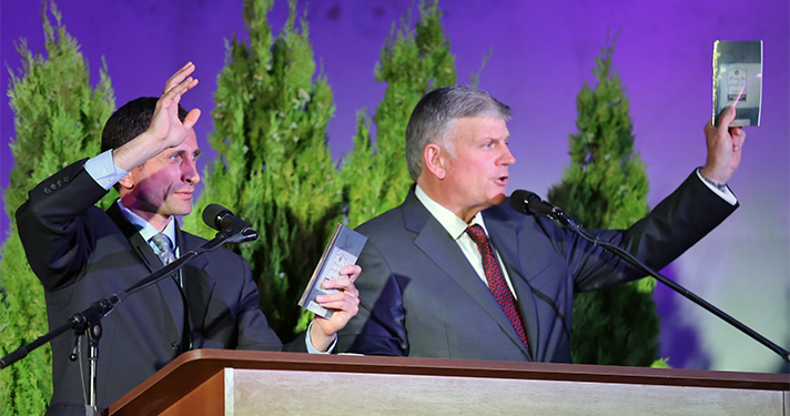 Franklin Graham holds up Georgian discipleship materials given to all new believers.