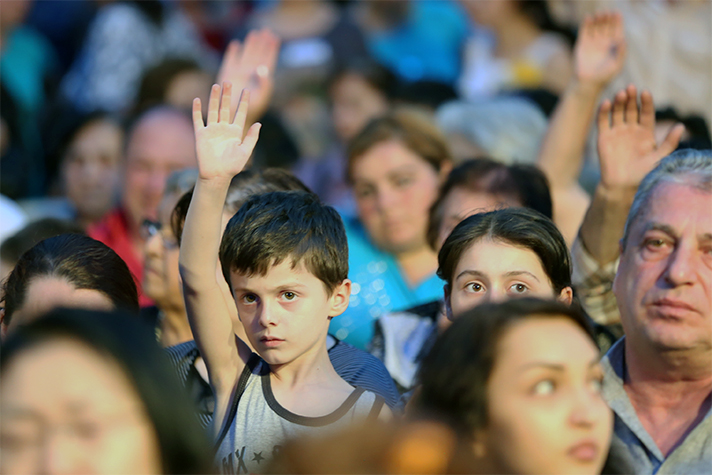 A Georgian boy raises his hand at Franklin Graham's invitation to accept Jesus at the Festival of Hope in Tbilisi. Hundreds made decisions for Christ for the second straight night.