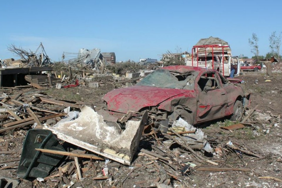 A mangled car stands in the rubble as a reminder of how devastating the EF-4 tornado was on June 16.