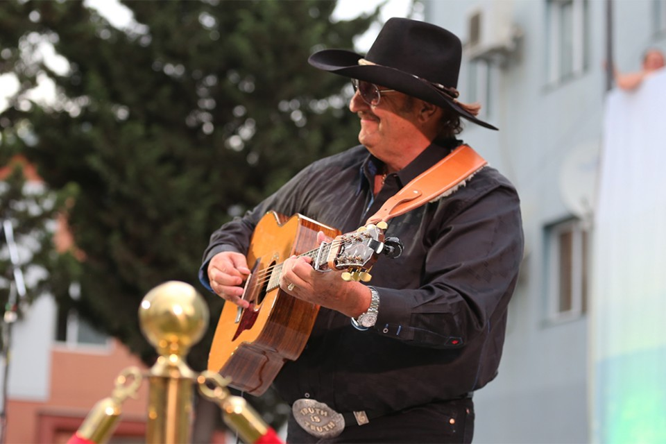 "Dennis Agajanian, known by some as the ""Armenian Cowboy"" because of his descent, played his usual fast-picking acoustic guitar."