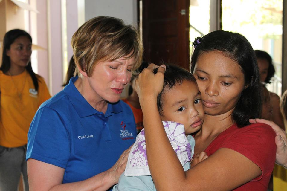 Rapid Response Team chaplain Barb Grabowski prays for a sick child in Cebu City, Philippines. The Rapid Response Team has been serving the areas hit by Hurricane Yolanda, encouraging and training pastors for the past six months.