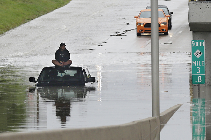 A stranded motorist sits on top of his car as he awaits rescue from a flooded freeway in Michigan. The Rapid Response Team has deployed chaplains to the Michigan flooding to help provide emotional and spiritual care.