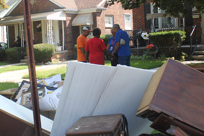 Chaplains with the Rapid Response Team pray with homeowners in Michigan on Monday.