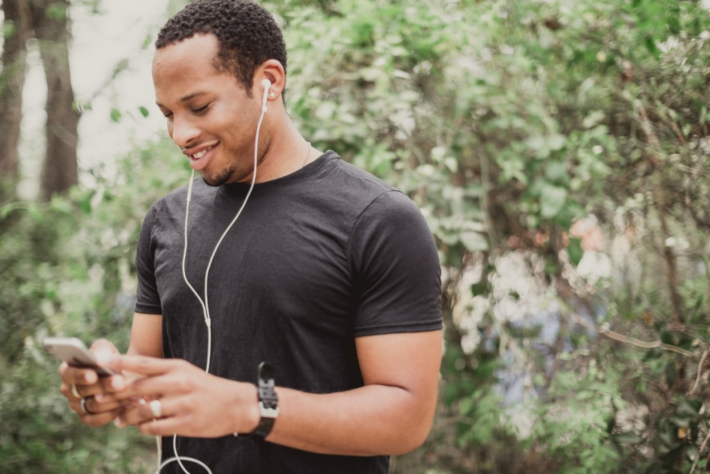 young man listening to podcast on his phone