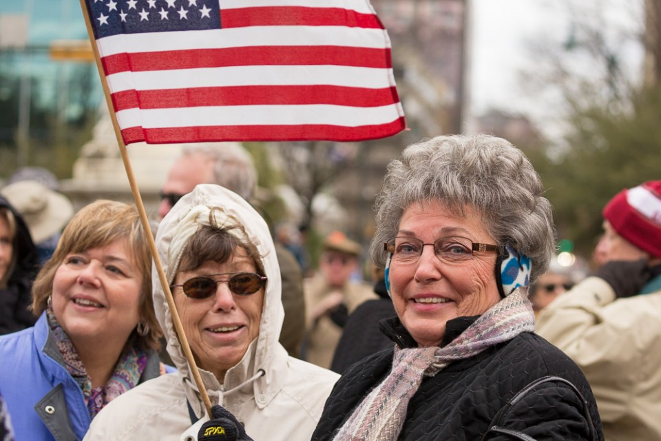 2 women dressed warm, with flag