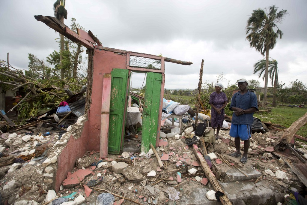 couple standing in ruins of home in Haiti
