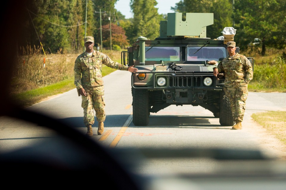 Two National Guard members stand beside Humvee
