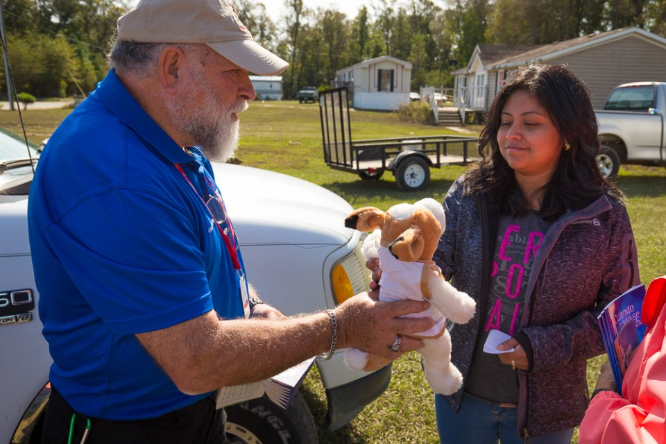 Chaplain hands stuffed animal (dog) to flood victim for her daughter