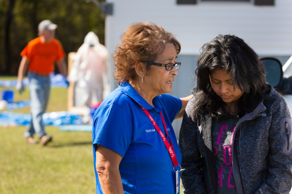 Billy Graham RRT Chaplain praying with woman (flood victim); men cleaning out underneath mobile home