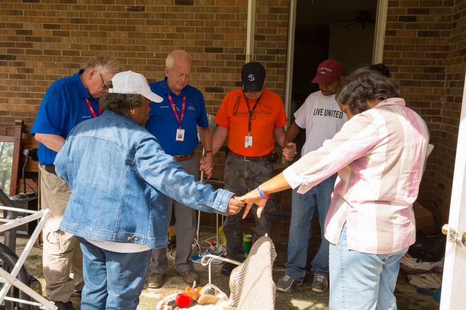 RRT chaplains circled up, holding hands with flood victims, praying