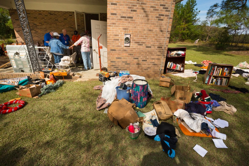 Household items, furniture, clothing on grass outside flooded house