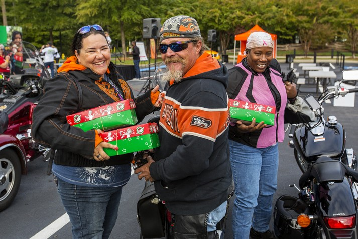 Bikers holding green and red shoeboxes, smiling