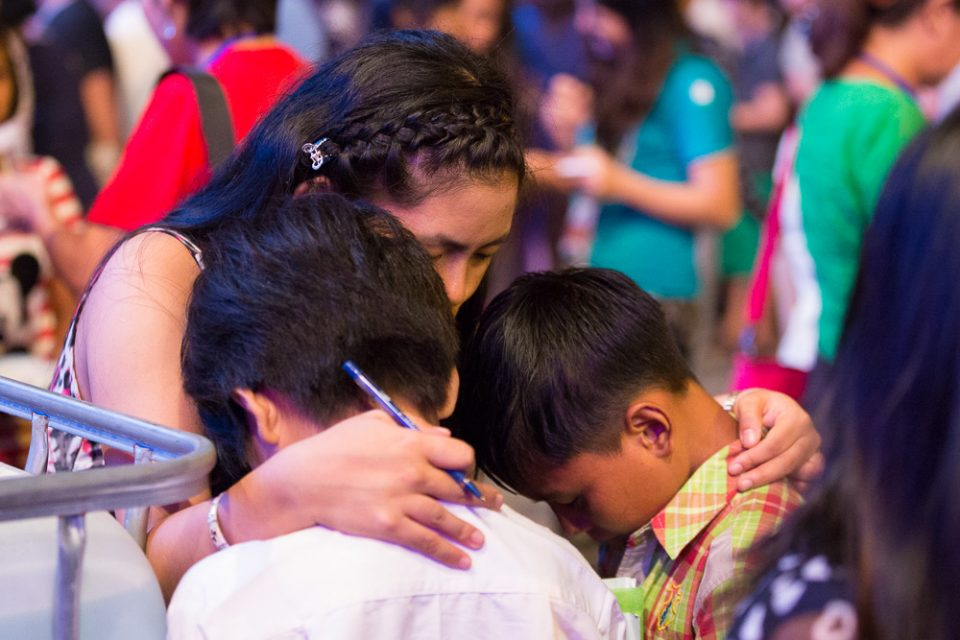 Counselor prays with two young boys
