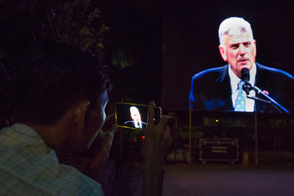 Man recording Franklin Graham's message on cell phone
