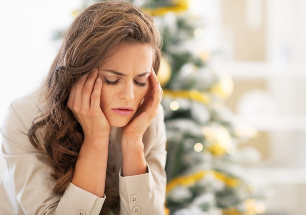 portrait of stressed young woman near christmas tree