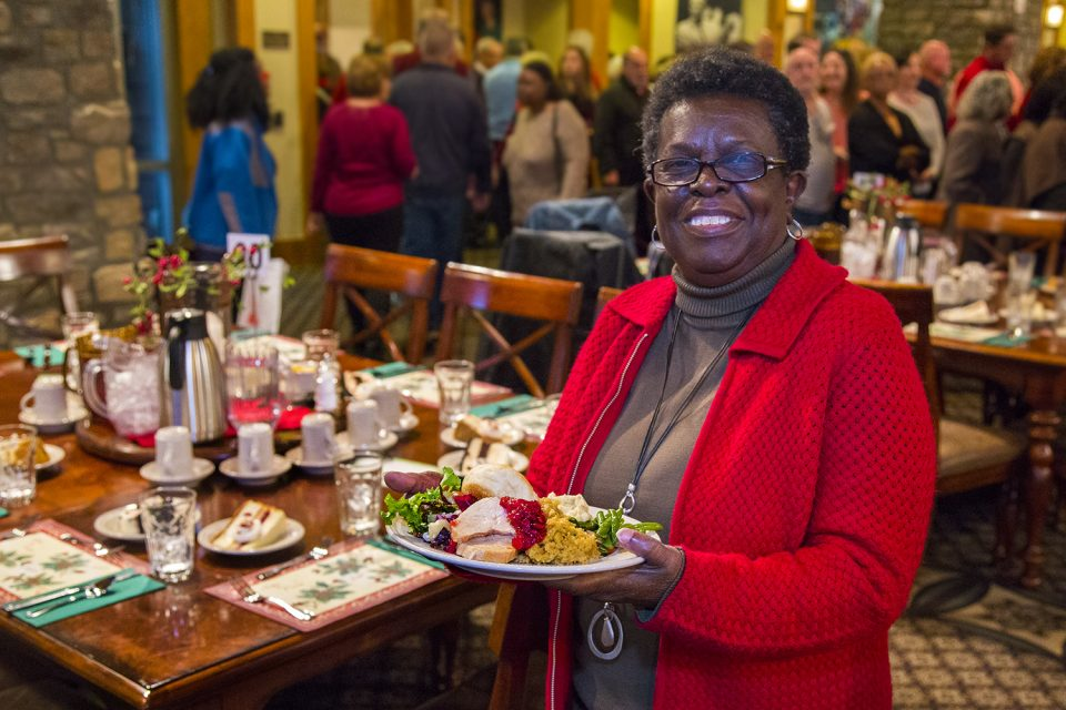 Woman holding full plate of food, smiling