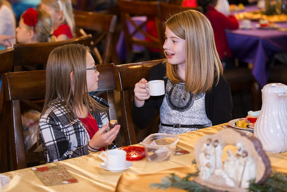 Two girls talking, eating treats, drinking hot chocolate