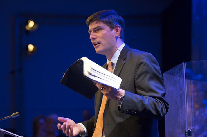 Will Graham preaching behind a pulpit, holding an open bible.