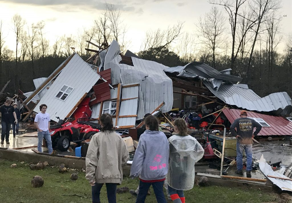 People examine a barn that was destroyed during a storm that swept through the southern U.S. on Monday, Jan. 2. (Source: Associated Press)