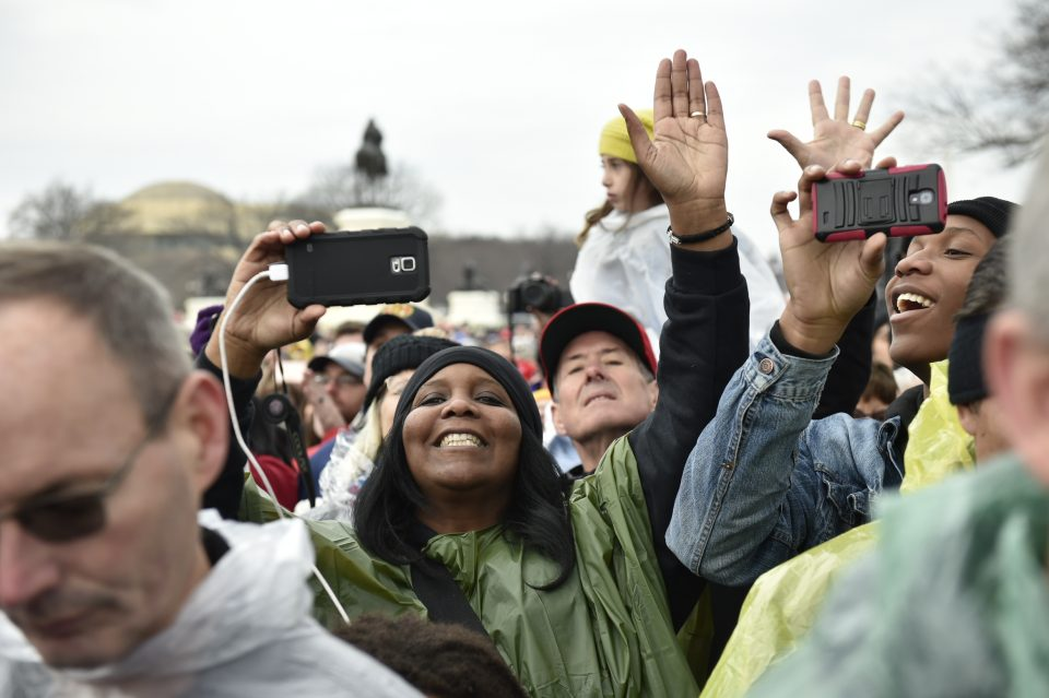 People holding up camera phones in crowd