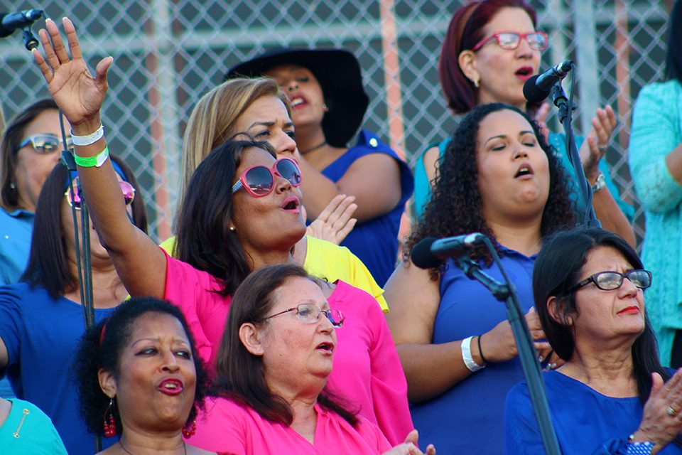 woman in pink shirt and sunglasses singing, arm outstretched