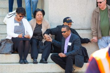People on steps of Maryland capital holding hands and praying