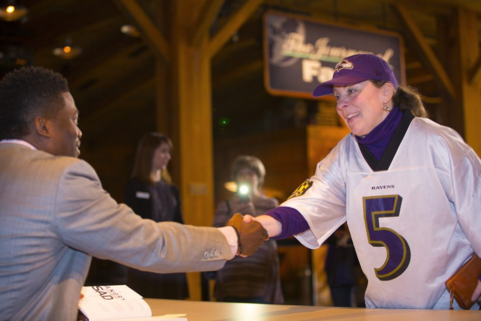 Watson shaking hands with woman in Baltimore Ravens jersey