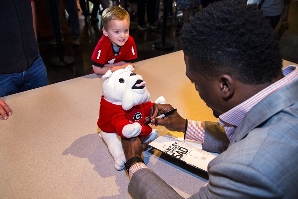 Watson signing Georgia Bulldog mascot while little boy looks on