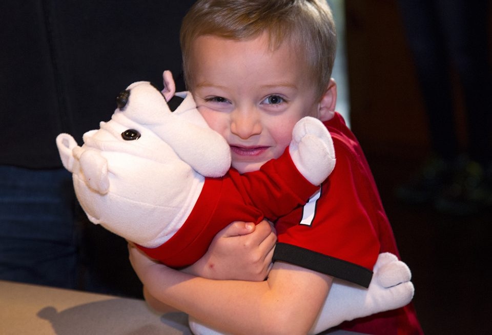 Little boy hugging Georgia Bulldog stuffed animal
