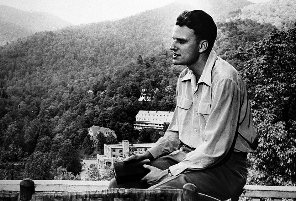 Billy Graham holding Bible, looking out at mountains